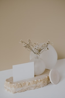 Pusta karta arkusza papieru z kopią makieta, suche kwiaty, marmurowy kamień na neutralnej beżowej ścianie.