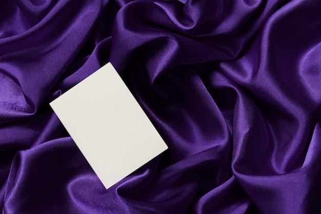Pusta karta na eleganckim fioletowym satynowym materiale w załamaniu. układ