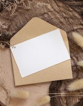 Pusta karta papierowa na kopercie i drewnianym stole z suszonymi roślinami wokół, widok z góry. scena makiety boho z szablonem zaproszenia