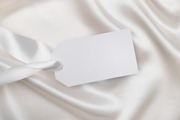Pusta karta tag dla tekstu na białej jedwabnej tkaninie. makieta do projektowania