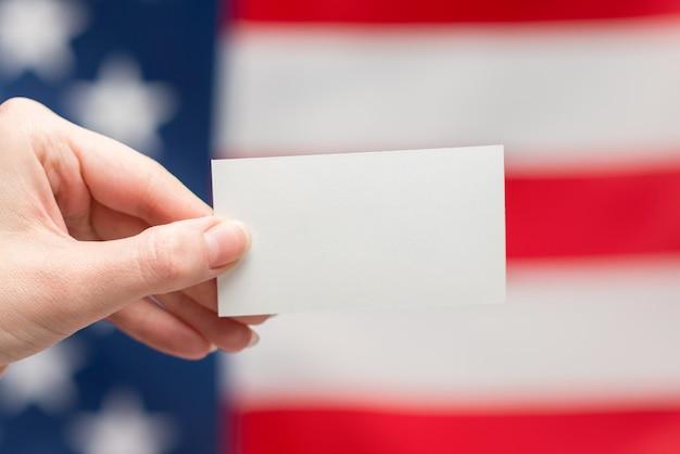 Pusta karta w ręce kobiety. skopiuj miejsce. powierzchnia flagi amerykańskiej