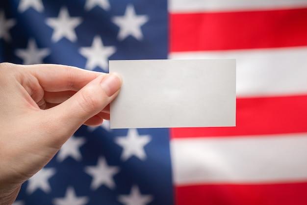 Pusta karta w ręce kobiety. skopiuj miejsce. powierzchnia flagi amerykańskiej.