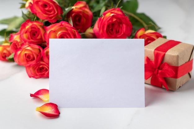 Pusta karta z pozdrowieniami, pudełko i bukiet róż na marmurowym stole, makieta do projektu