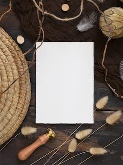 Pusta karta zaproszenie na ciemny brązowy drewniany stół z artystycznymi dekoracjami wokół widoku z góry. scena makiety boho z szablonem kartki z życzeniami