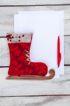 Pusta kartka papieru na drewnianym stole z długopisem i świąteczną zabawką.
