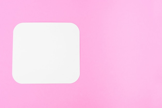 Pusta kartka papieru na różowym tle, miejsce na tekst. pusta karta
