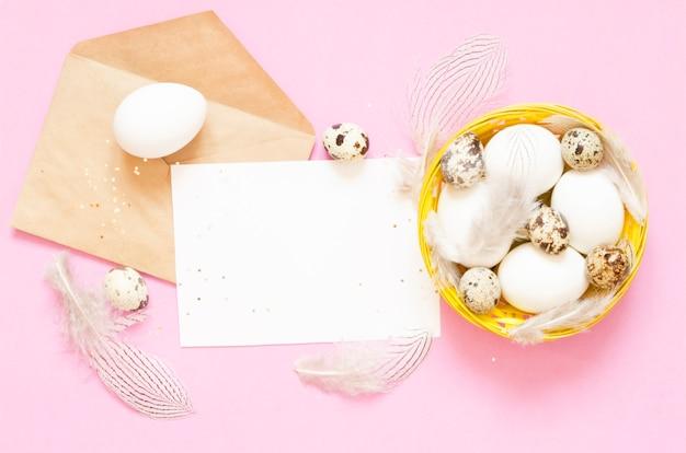 Pusta kartka z pozdrowieniami, koperta kraft. wielkanocni jajka w koszu. płaski układ, widok z góry.