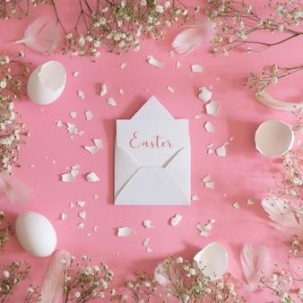 Pusta kartka z życzeniami, koperta kraft. pisanki i kwiaty łyszczec na różowym tle. widok płaski, widok z góry.