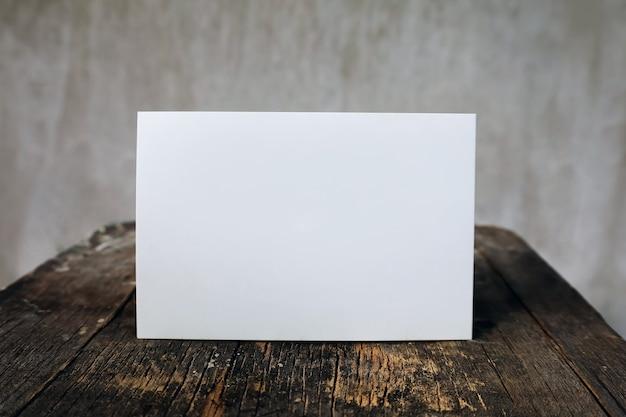 Pusta kartka z życzeniami na drewnianym stole vintage i tle ściany, list makieta