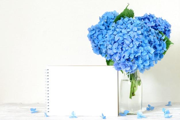 Pustą kartkę z życzeniami i niebieskie kwiaty hortensji na biały drewniany stół. ślub lub wiosenne wakacje koncepcja