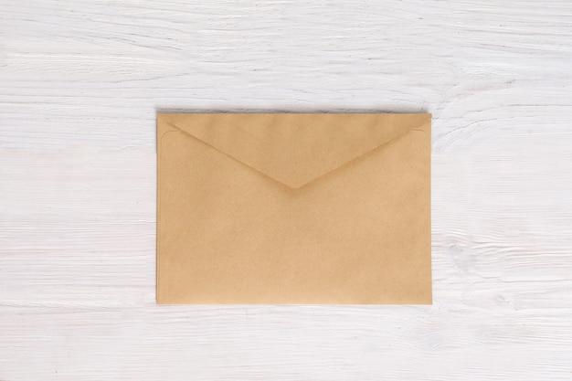 Pusta koperta pusta na białym drewnianym, płaskim lay