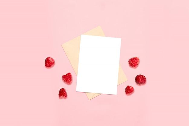Pusta koperta z kartką papieru, ozdobiona rodzimymi malinami, widok z góry