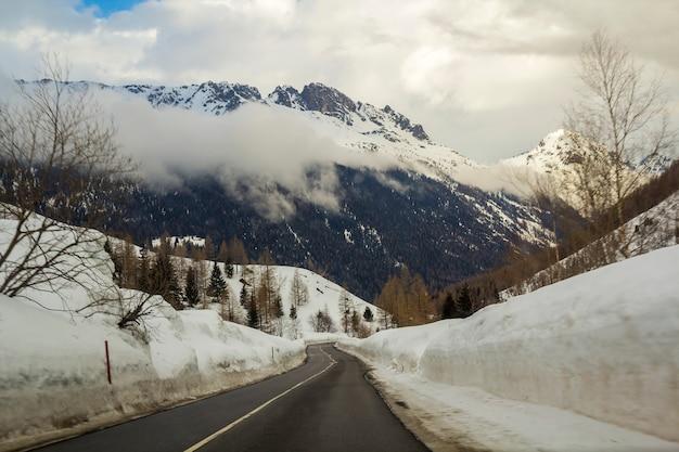 Pusta kręta asfaltowa droga rozciągająca się przez głęboki śnieg w kierunku pięknych jasnych białych alp
