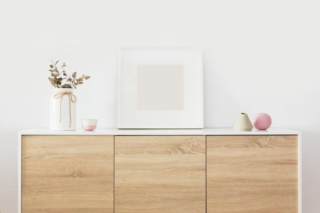 Pusta kwadratowa biała ramka we wnętrzu salonu z północną dekoracją
