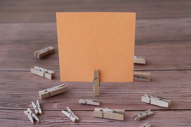 Pusta kwadratowa notatka otoczona spinaczami do prania pokazująca nowe znaczenie pustego kawałka lepkiego papieru