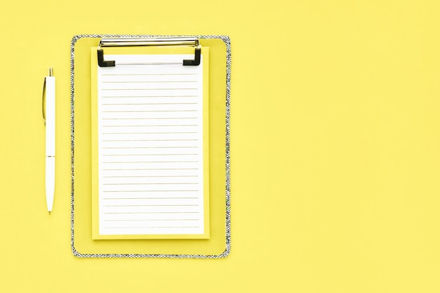 Pusta makieta schowka i biały długopis na żółtym stole. powrót do szkoły, ostateczny termin