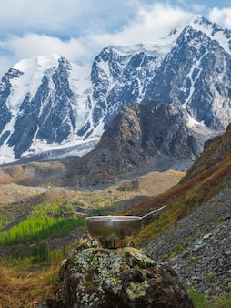 Pusta miska turystyczna z łyżką ułożona jest na kamieniu na tle lodowca i wysokich gór. pora obiadowa, trekking wysokogórski. widok pionowy.