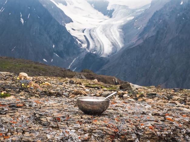 Pusta miska turystyczna z łyżką ułożona jest na kamieniu na tle lodowca i wysokich gór. pora obiadowa, trekking wysokogórski.
