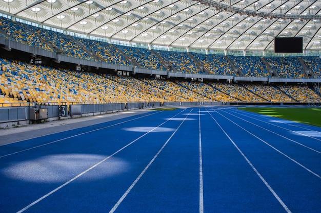 Pusta niebieska bieżnia na stadionie olimpijskim na tle pustych trybun