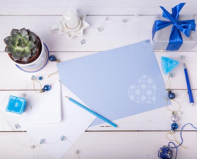 Pusta niebieska kartka z życzeniami z białą kopertą, prezentem, soczystymi i świątecznymi dekoracjami. leżał z płaskim, tło, widok z góry.