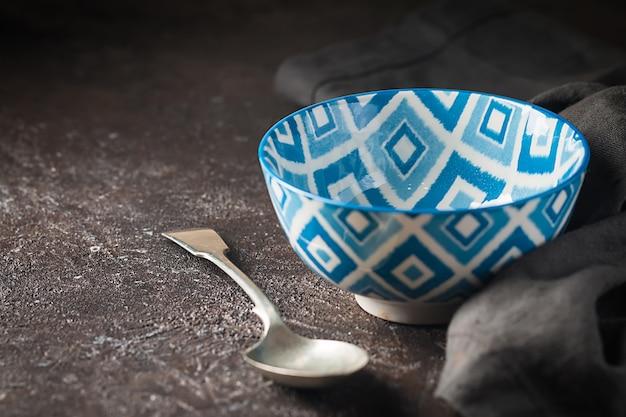 Pusta niebieska orientalna miska z łyżką na ciemnej powierzchni kamienia.