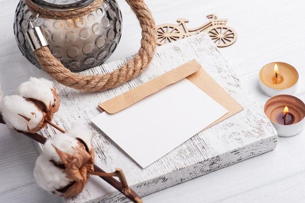 Pusta notatka i koperta kraft z zapalonymi świecami