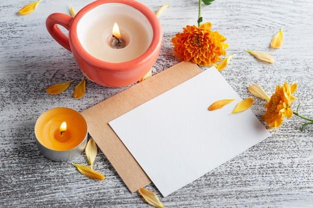 Pusta notatka i pomarańczowa świeca zapachowa i kwiaty