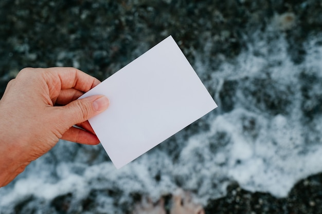 Pusta notatka papierowa w ręku w niesamowitym tle krajobrazu. koncepcja podróży i wakacji. biała kartka papieru bez tekstu.
