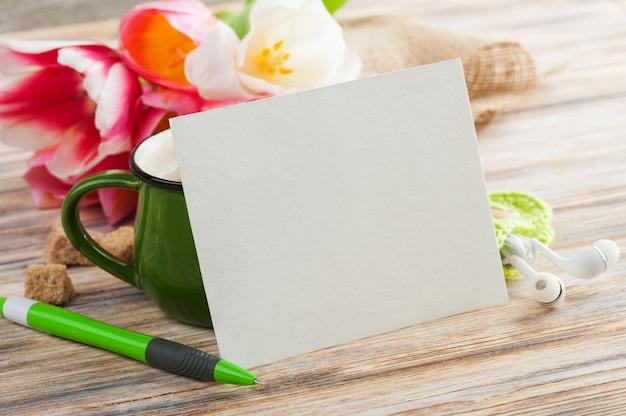 Pusta notatka papierowa, zielony długopis, słuchawki i kubek kawy