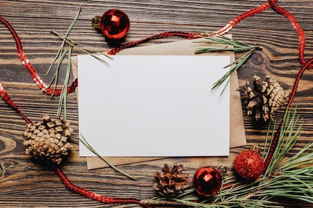 Pusta notatka z gałąź jodła i świąteczne zabawki na podłoże drewniane. koncepcja nowego roku