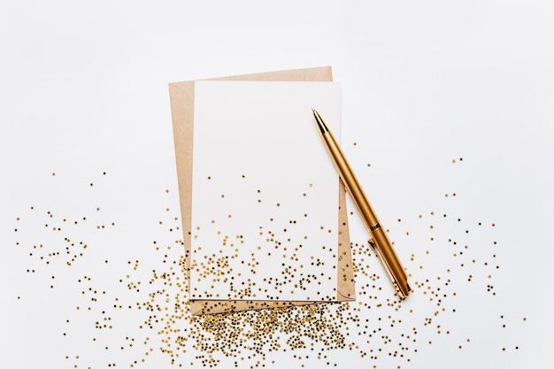 Pusta notatka z kopertą, długopisem i złotymi brokatowymi gwiazdkami na białym tle