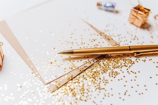 Pusta notatka z kopertą, długopisem i złotymi gwiazdami brokat na białym tle