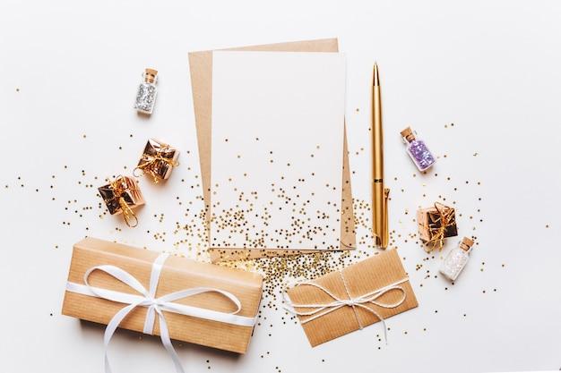 Pusta notatka z kopertą, prezentami, długopisem i złotymi gwiazdami brokat na białym tle