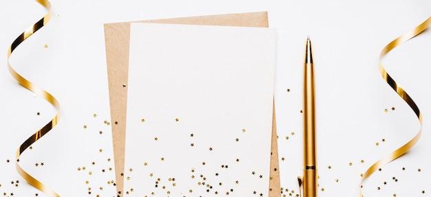 Pusta notatka z kopertą, wstążką, konfetti, długopisem i złotymi gwiazdami brokatu na białej ścianie