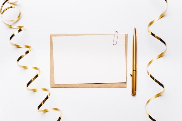 Pusta notatka z koperty, długopis, prezenty i złota wstążka na białym tle