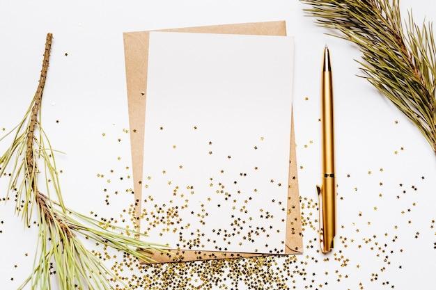 Pusta notatka z koperty, gałęzi świerku i złotym piórem na białym tle