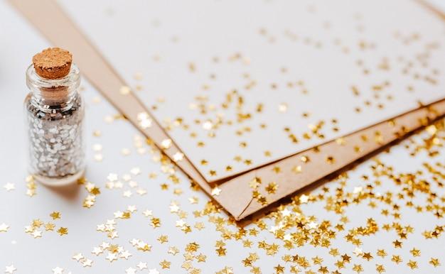 Pusta notatka z koperty, prezenty i złote gwiazdy brokat na białym tle