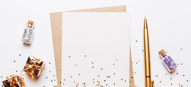 Pusta notatka z prezentami, długopisem i złotymi gwiazdami brokatu
