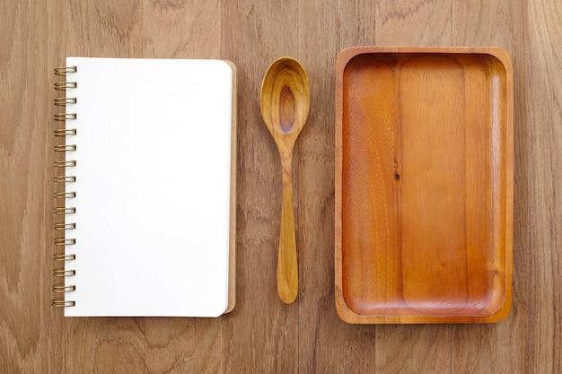 Pusta nutowa książka, drewniany talerz i łyżka na stole ,.