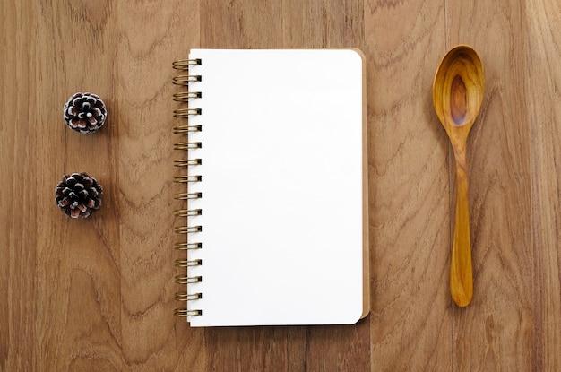 Pusta nutowa książka i drewniana łyżka na stole