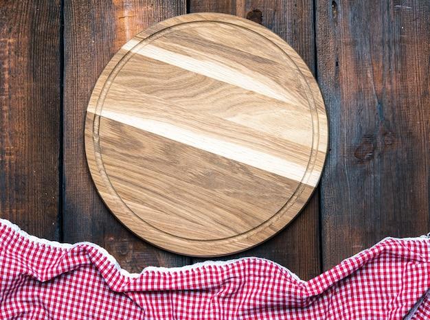 Pusta okrągła drewniana deska do krojenia i czerwona serwetka na brązowym stole, widok z góry
