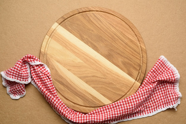 Pusta okrągła drewniana deska do pizzy na brązowym tle, widok z góry