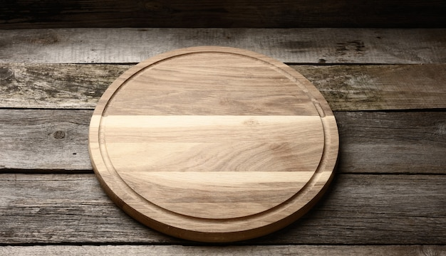 Pusta okrągła drewniana deska kuchenna do krojenia na drewnianym tle, deska do pizzy, widok z góry
