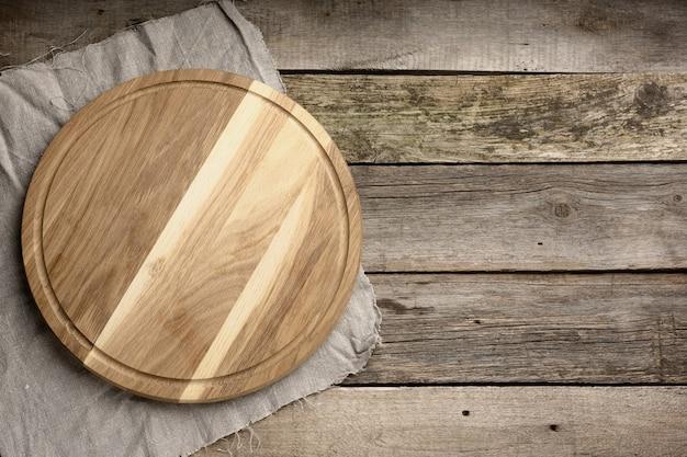 Pusta okrągła drewniana deska kuchenna do krojenia na powierzchni drewnianej, deska do pizzy, miejsce na kopię