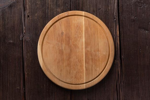 Pusta okrągła pizza lub deska do grillowania na ciemnym drewnianym stole