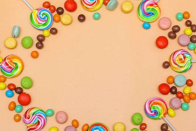 Pusta okrągła rama wykonana z różnych kolorowych cukierków na kremowym tle płaski widok z góry