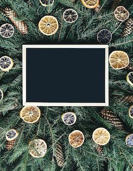 Pusta oprawione deska na zielone gałęzie jodły ozdobione suszonymi plasterkami pomarańczy i szyszek. boże narodzenie i nowy rok rocznika zimowych świąteczna kompozycja.