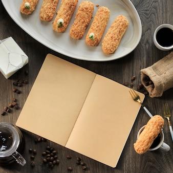 Pusta otwarta książka dla książki kucharskiej/przepis/tekst z widelcem do ciasta, craquelin eclair, ziarnami kawy, dzbankiem do kawy i mlekiem. koncepcja książki menu na brązowym drewnianym tle