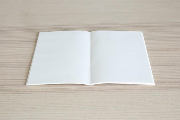 Pusta otwarta książka papierowa na drewnianym stole
