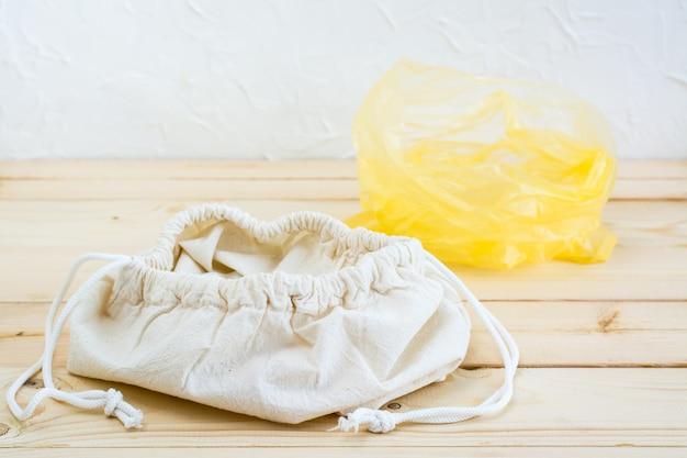 Pusta otwarta płócienna torba z opaskami na żywność i plastikowa torba na naturalnym drewnianym tle